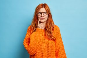 Portrait of attractive redhead young woman keeps index finger near corner of lips overthinks somethi