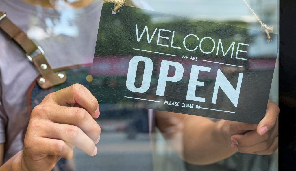 Close-up of the Business owner hand holding an open sign for service.